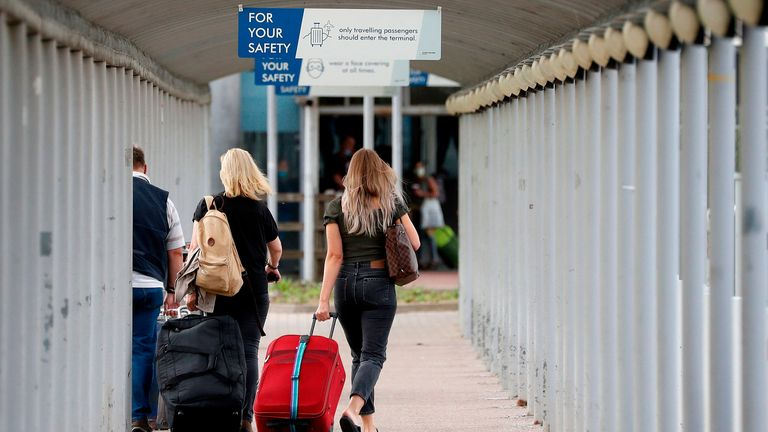 Travellers pull their suitcases as they arrive at London Stansted Airport, northeast of London on August 20, 2020 following the decision by British no-frills airline Easyjet to close its operations at the airport from August 31. (Photo by Adrian DENNIS / AFP) (Photo by ADRIAN DENNIS/AFP via Getty Images)