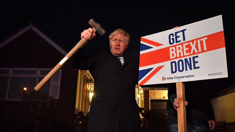 """TOPSHOT - Britain's Prime Minister and Conservative party leader Boris Johnson poses after hammering a """"Get Brexit Done"""" sign into the garden of a supporter, with a sledgehammer as he campaigns with his team in Benfleet, east of London on December 11, 2019, the final day of campaigning for the general election. - Britain will go to the polls tomorrow to vote in a pre-Christmas general election. (Photo by Ben STANSALL / POOL / AFP) (Photo by BEN STANSALL/POOL/AFP via Getty Images)"""