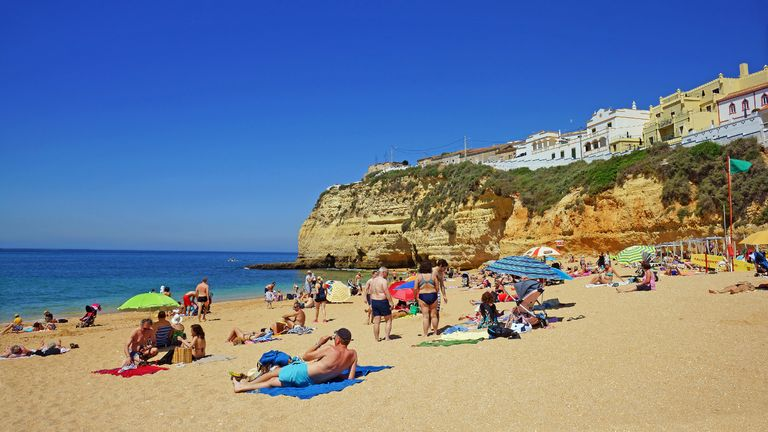 Holiday makers enjoying the blue sky day on Praia da Cavoeiro, The Algarve, Portugal,