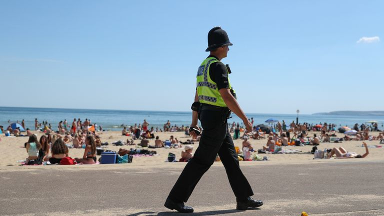 A police officer patrols along the beach in Bournemouth, Dorset, as the public are being reminded to practice social distancing following the relaxation of the coronavirus lockdown restrictions in England.