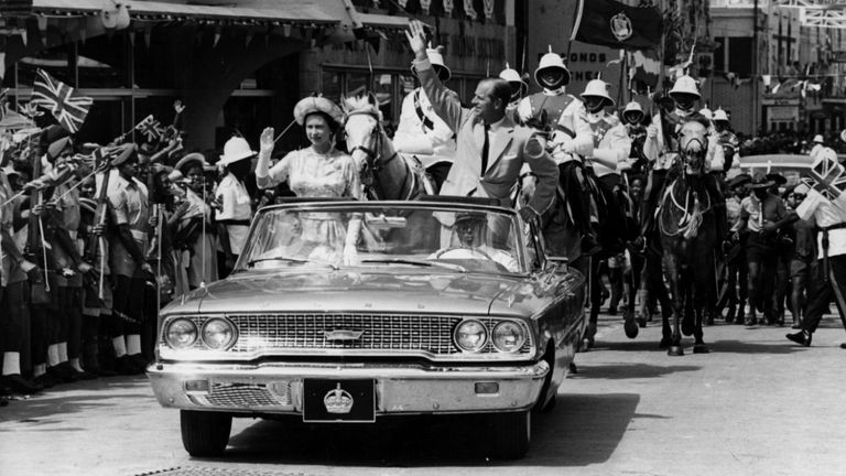 18th February 1966:  The Queen and Prince Philip driving through Barbados waving to the crowds.  (Photo by Keystone/Getty Images)