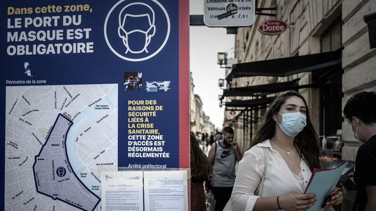 A woman wearing a protective face mask walks past a sign showing the area where wearing a protective mask is mandatory, due to the Covid-19, in Bordeaux, southwestern France, on September 16, 2020. (Photo by Philippe LOPEZ / AFP) (Photo by PHILIPPE LOPEZ/AFP via Getty Images)