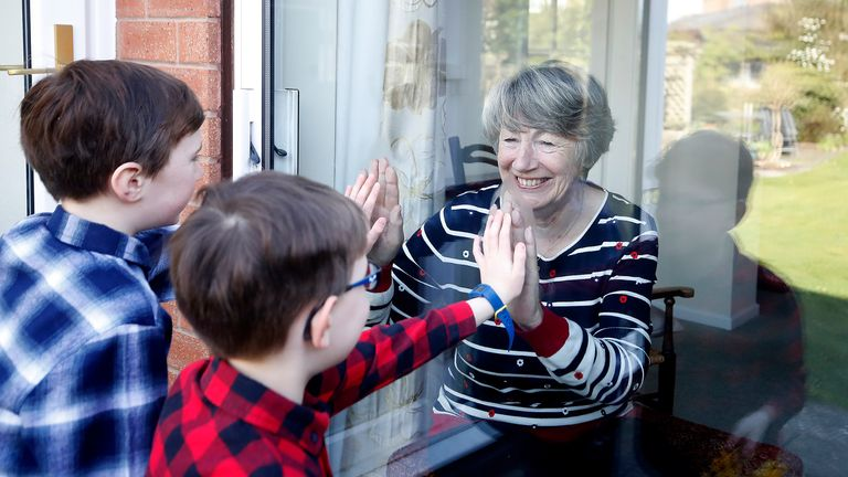 Ben and Isaac talk to their grandmother Sue through a window, as she and her husband Alan self-isolate due at their home in Knutsford, Cheshire.