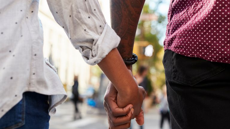 Close Up Of Couple Holding Hands On Urban Street