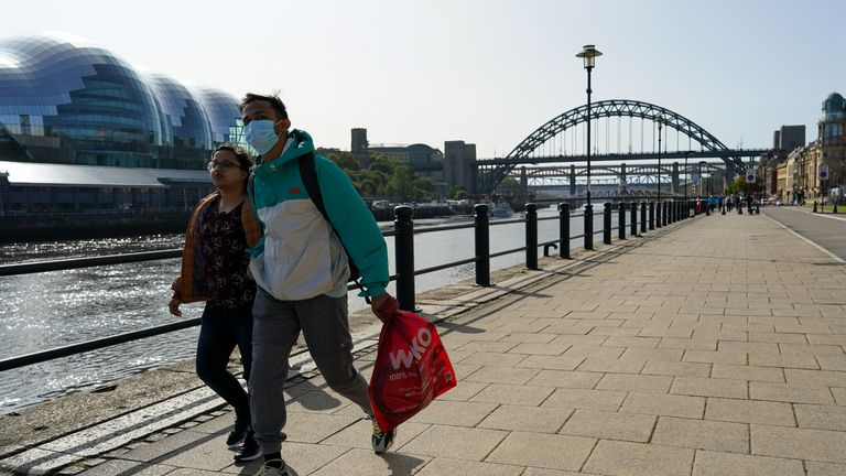 NEWCASTLE UPON TYNE, ENGLAND - SEPTEMBER 17: A couple walk along Newcastle quayside on September 17, 2020 in Newcastle upon Tyne, England. Almost two million people in north-east England will be banned from mixing with other households and pubs will close early as coronavirus cases rise. Health Secretary Matt Hancock announced the temporary restrictions will be in place from midnight due to concerning rates of infection. The measures affect seven council areas, Newcastle, Northumberland, North Tyneside, South Tyneside, Gateshead, County Durham and Sunderland. (Photo by Ian Forsyth/Getty Images)