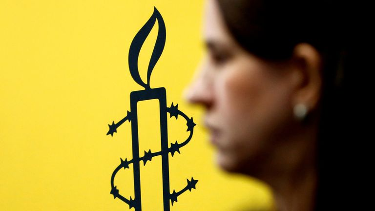 The logo of Amnesty International is seen next to director of Mujeres En Linea Luisa Kislinger, during a news conference in Caracas