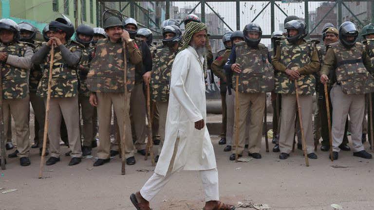 A Muslim man walks past policemen standing guard next to a mosque in a riot affected area following clashes between people demonstrating for and against a new citizenship law in New Delhi
