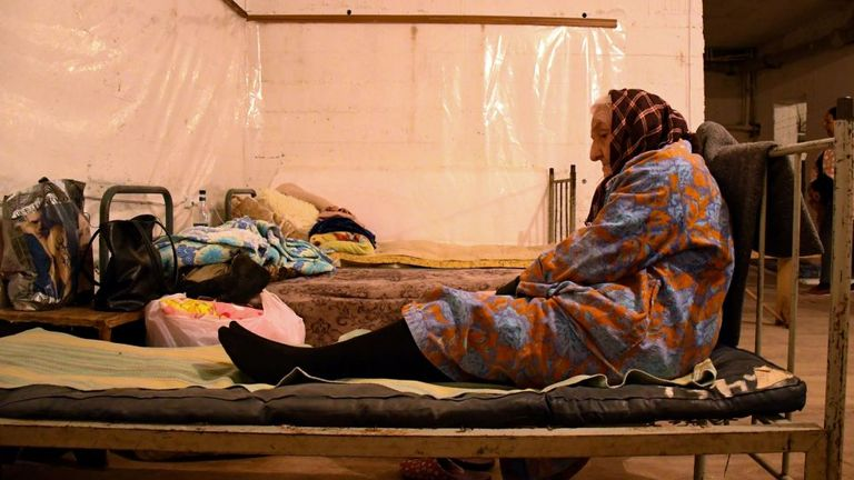 A elderly woman sits on a bed in a building's basement used as a bomb shelter in Nagorny Karabakh's main city of Stepanakert