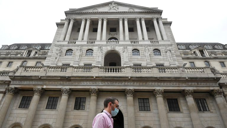 A worker wearing a protective face mask walks past the Bank of England in the City of London, Britain, August 6, 2020.