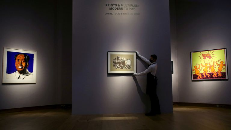 An employee holds a work by Banksy at Christie's auction house in London, Britain September 9, 2020. REUTERS/Tom Jacobs NO RESALES. NO ARCHIVES.