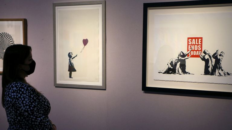 A woman poses near works by Banksy at Christie's auction house in London, Britain September 9, 2020. REUTERS/Tom Jacobs NO RESALES. NO ARCHIVES.