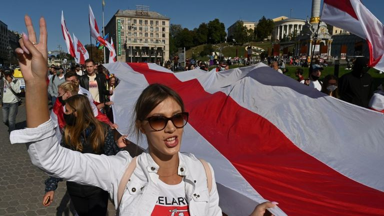 Members of the Belarusian diaspora and Ukrainian activists hold former white-red-white Belarus flags during a rally in support of Belarusians protesting against presidential election results, in Kiev on September 20, 2020. (Photo by Genya SAVILOV / AFP) (Photo by GENYA SAVILOV/AFP via Getty Images)