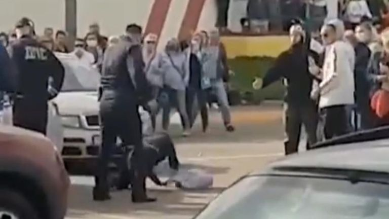 A woman was punched to the ground during an altercation between police and local protesters in Zhodzina, Belarus