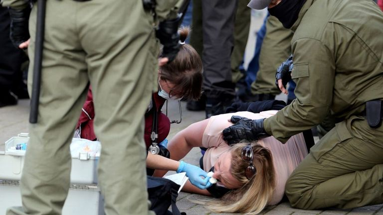 A nurse provides medical care to a woman laying on the ground as law enforcement officers stand next to them during a rally to protest against the presidential election results in Minsk on September 19, 2020. - Belarus President Alexander Lukashenko, who has ruled the ex-Soviet state for 26 years, claimed to have defeated opposition leader Svetlana Tikhanovskaya with 80 percent of the vote in the August 9, elections. (Photo by - / TUT.BY / AFP) (Photo by -/TUT.BY/AFP via Getty Images)