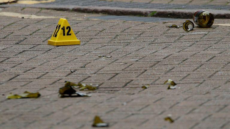 A broken glass bottle is seen near an evidence marker after reported stabbings in Birmingham, Britain