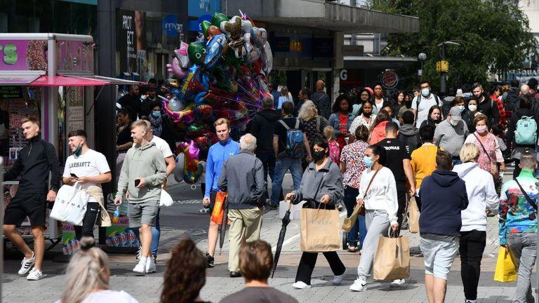 People are seen walking down a high street in Birmingham during the coronavirus pandemic