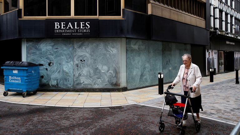 An elderly lady is seen walking pasted a closed shop as coronavirus restrictions are in place in Bolton