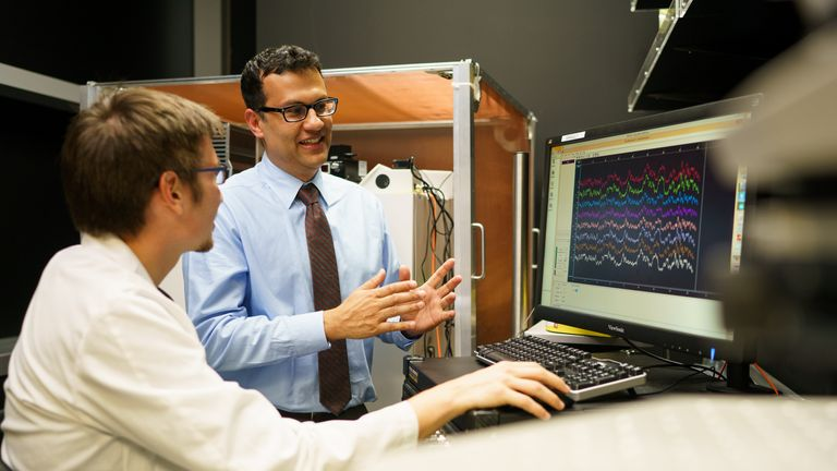 Karunesh Ganguly, MD, discusses ECoG brain recording data with student Stefan Lemke in 2016 (Credit UCSF).jpg