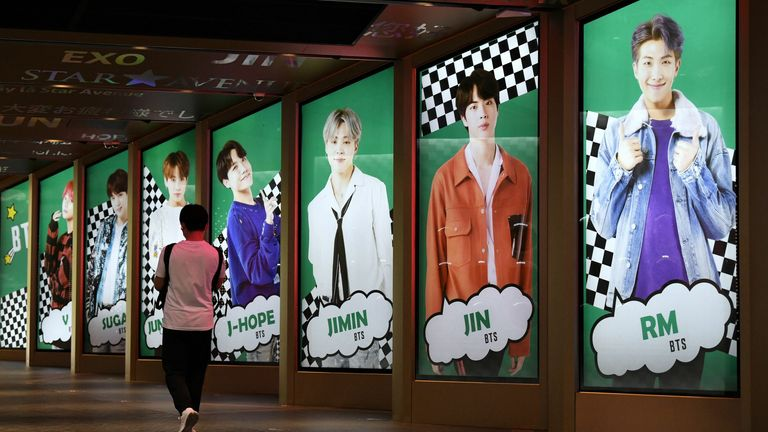 A man walks past commercial posters showing K-pop group BTS members outside a duty free shop in Seoul on September 1, 2020.