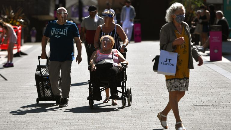 Shoppers wear face masks in Burnley town centre on July 31, 2020 in Burnley, England. Lockdown has been heightened in parts of England with a restriction ban for separate households in parts of northern England from meeting each other at home.
