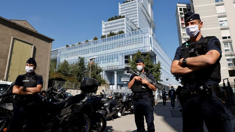 Police officers stand guard outside Paris' courthouse