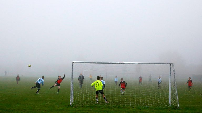 Children play a Sunday League football match during low fog in Netherley Liverpool.