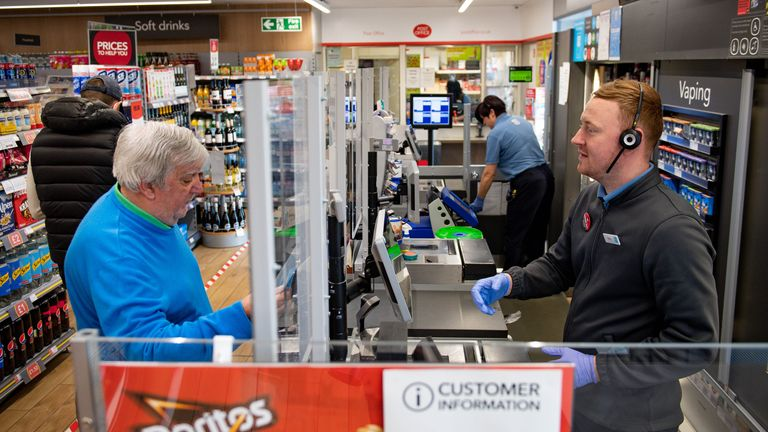 A clear screen divides employees and customers in store at a Co-op shop in Bromsgrove, Worcestershire