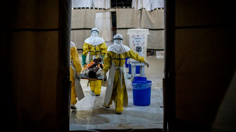 Health workers move an Ebola patient