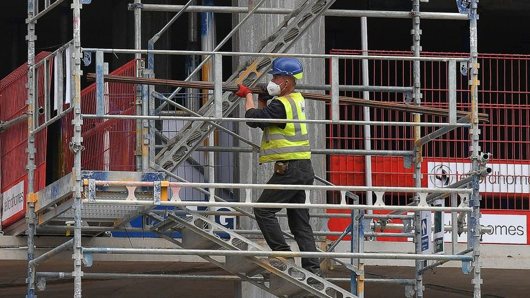 Construction workers wearing PPE (personal protective equipment), some including face masks, work to build new apartments and a retail complex at Nine Elms in south London on May 14, 2020 following an easing of the novel coronavirus COVID-19 lockdown guidelines. -