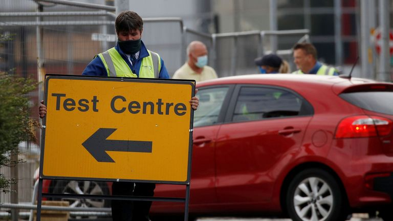 A worker carries an information sign as a coronavirus