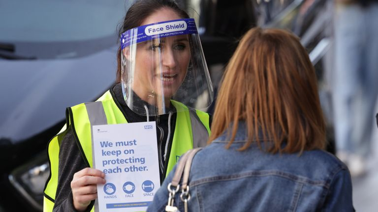 A woman handing out leaflets promoting the new NHS Covid-19 app in Liverpool.