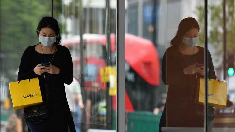 A shopper uses her phone as she wears a mask as a precaution against the transmission of the novel coronavirus as she walks past a shop window on Oxford Street in London on July 14, 2020. - Face masks will be compulsory in shops and supermarkets in England from next week, the government said on July 14, in a U-turn on previous policy. (Photo by JUSTIN TALLIS / AFP) (Photo by JUSTIN TALLIS/AFP via Getty Images)