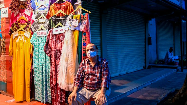 A man waits for customers at his clothing store in New Delhi