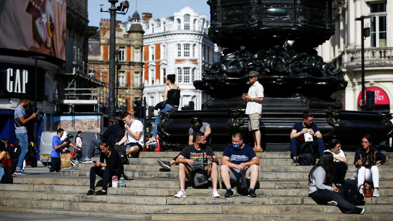People sit on steps at Piccadilly Circus in central London