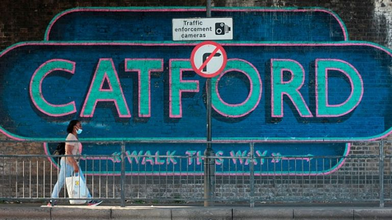 A woman walks past a sign in Catford, southeast London