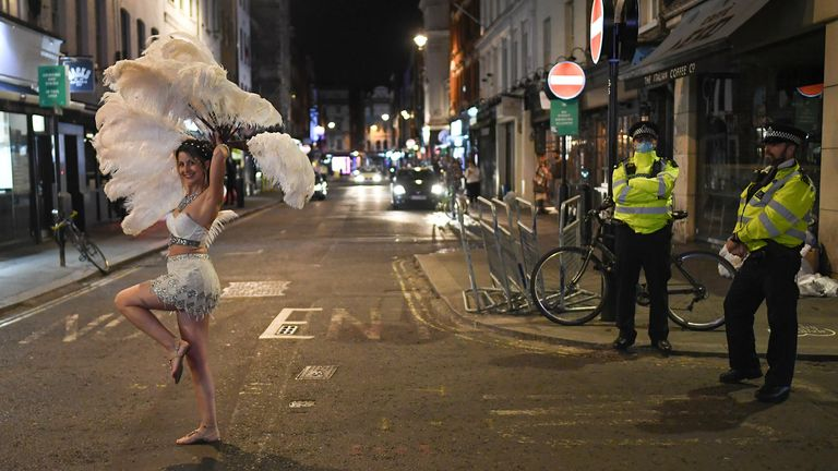 Police look on as an entertainer walks past in Soho