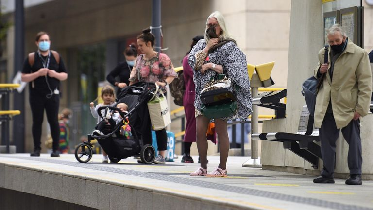 "Commuters, some wearing face masks or covering due to the COVID-19 pandemic, stand on the platform of a tram station in Manchester, northwest England on August 3, 2020, following a rise in the number of COVID-19 cases in the region. - Britain on Friday ""put the brakes on"" easing lockdown measures and imposed new rules on millions of households in northern England, following concerns over a spike in coronavirus infections. The government increased regional lockdown measures -- under which people"
