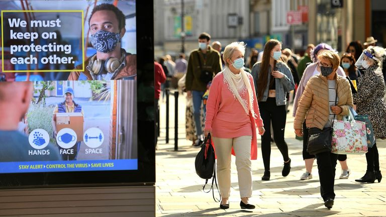 "Shoppers, some wearing a face mask or covering, walk past an electronic billboard displaying a UK Government advert advising the public to take precautions to mitigate the spread of COVID-19, in Newcastle city centre, north-east England, on September 17, 2020. - The British government on Thursday announced new restrictions for northeast England, the latest region to see a surge in coronavirus cases as Prime Minister Boris Johnson warned of a ""second hump"" in nationwide transmission. Residents in"