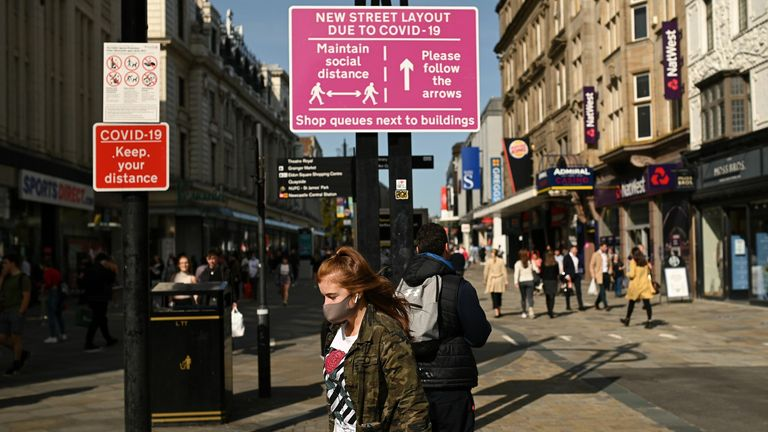 """BRITAIN-HEALTH-VIRUS Shoppers, some wearing a face mask or covering due to the COVID-19 pandemic, walk past a sign alerting pedestrians to a one-way system to assist with social distancing, in Newcastle city centre, north-east England, on September 17, 2020. - The British government on Thursday announced new restrictions for northeast England, the latest region to see a surge in coronavirus cases as Prime Minister Boris Johnson warned of a """"second hump"""" in nationwide transmission. Residents in t"""