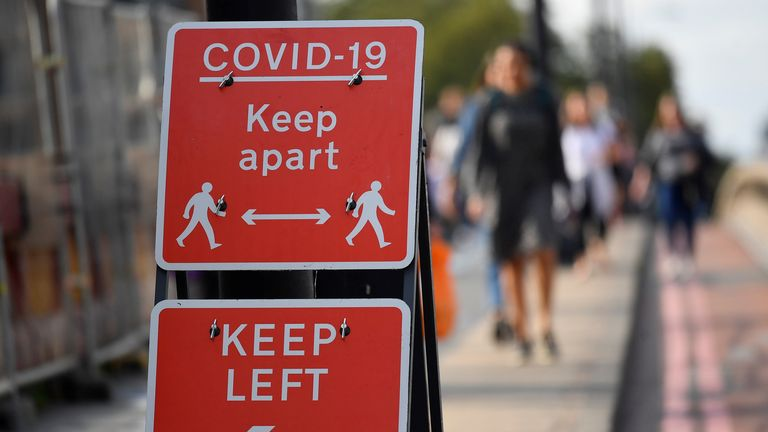 Pedestrians walk near public health signs in London, as  the number of COVID-19 cases rises