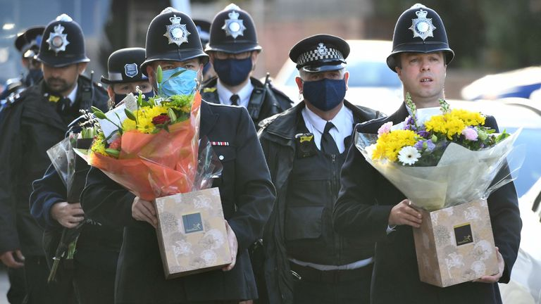 Met officers carry flowers to place at the scene in south London