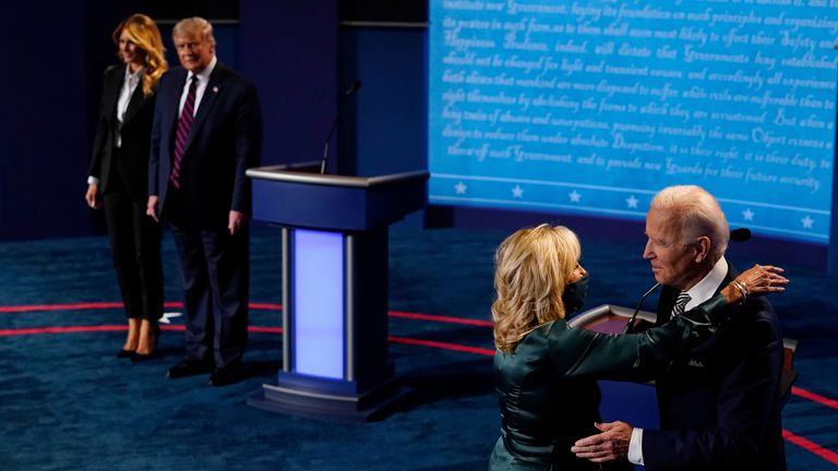First lady Melania Trump stands with President Donald Trump as he looks at Democratic presidential candidate former Vice President Joe Biden as he is hugged by his wife Jill Biden
