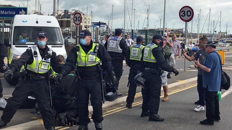 A man, restrained on the ground by police, is arrested, whilst other officers create a cordon to keep back anti-migrant protesters who are demonstrating in Dover against immigration and the journeys made by refugees crossing the Channel to Kent