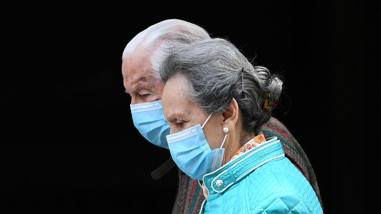TOPSHOT - An elderly couple wearing face masks walks in Madrid on April 30, 2020 during a national lockdown to prevent the spread of the COVID-19 disease. - Spain counted another 268 people who have died from the coronavirus, the lowest daily number since March 20 as the country prepares to ease its tough lockdown measures. (Photo by Gabriel BOUYS / AFP) (Photo by GABRIEL BOUYS/AFP via Getty Images)