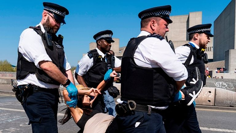Four officers are seen arresting one 'limp' XR protester