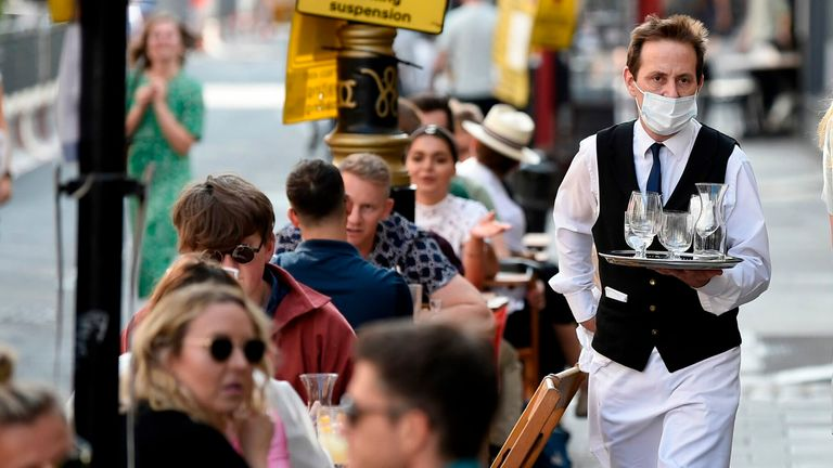 A waiter wearing a protective face mask serves customers at tables outside a restaurant in Soho, in London on September 20, 2020 as the British government consider fresh nationwide restrictions after an rise in cases of the novel coronavirus. - The government this week tightened restrictions on socialising because of a surge in coronavirus cases, and imposed local lockdowns across swathes of the country. (Photo by DANIEL LEAL-OLIVAS / AFP) (Photo by DANIEL LEAL-OLIVAS/AFP via Getty Images)
