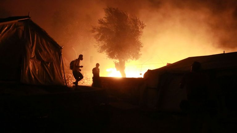 Migrants leave as a fire burns in the Moria camp on the island of Lesbos on September 9, 2020