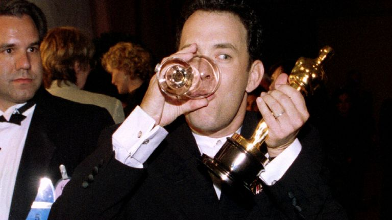 "Actor Tom Hanks sips a glass of water at the Governor's Ball March 27 as he holds the Oscar he won as best actor for his role in ""Forrest Gump"" at the 67th Academy Awards in Los Angeles"