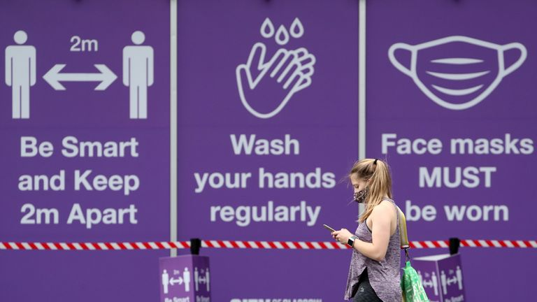 A member of the public walks passed coronavirus related signs at the City of Glasgow College