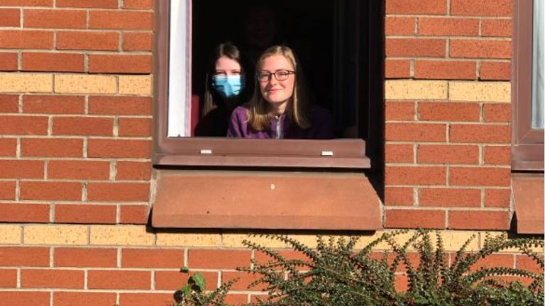 Harriet Sweatman (right) and her flatmate talk from their window